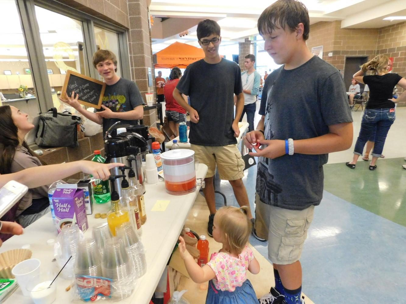 Students from The Mav gather around their fundraising stand at the Mead HS Round Up on August 18.