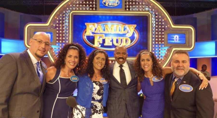 Officer Ish and his family pose with Steve Harvey on Family Feud.