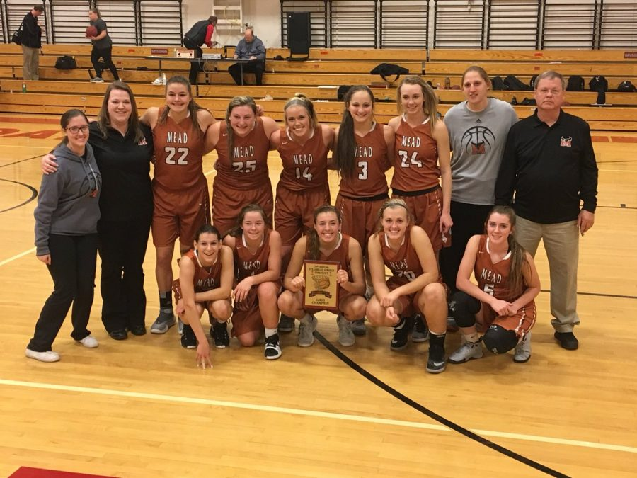 The Girls Varsity basketball team posing with their championship plaque after a victory against Moffat County (47-33), naming them the Steamboat Shootout champions.
