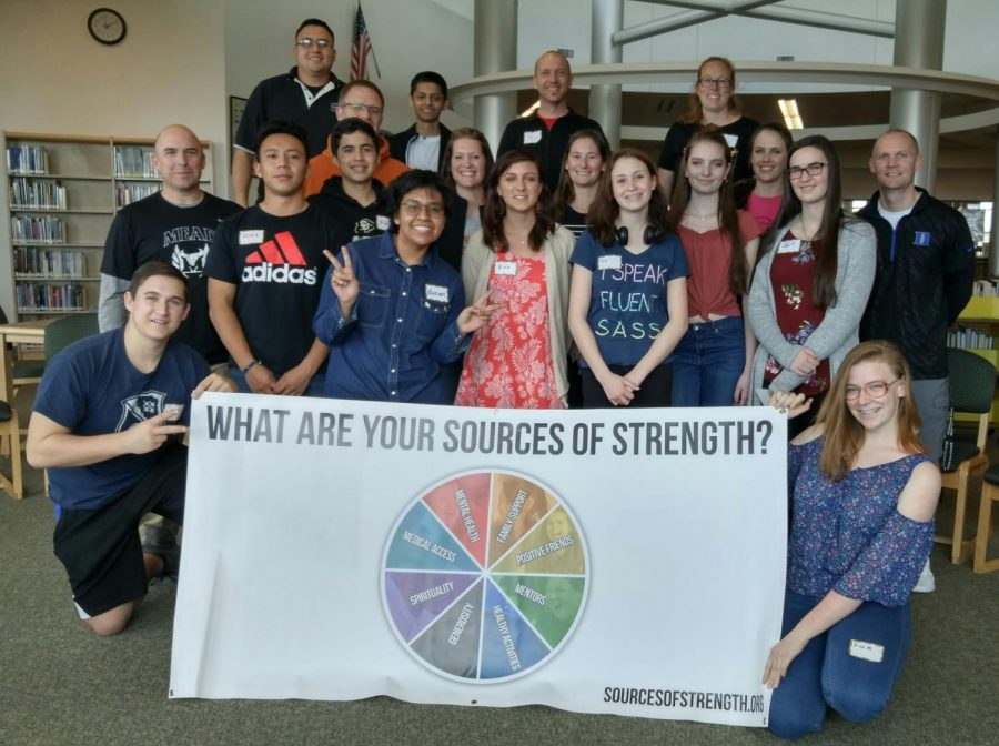Members of Sources of Strength here at Mead pose in front of the Sources of Strength banner.