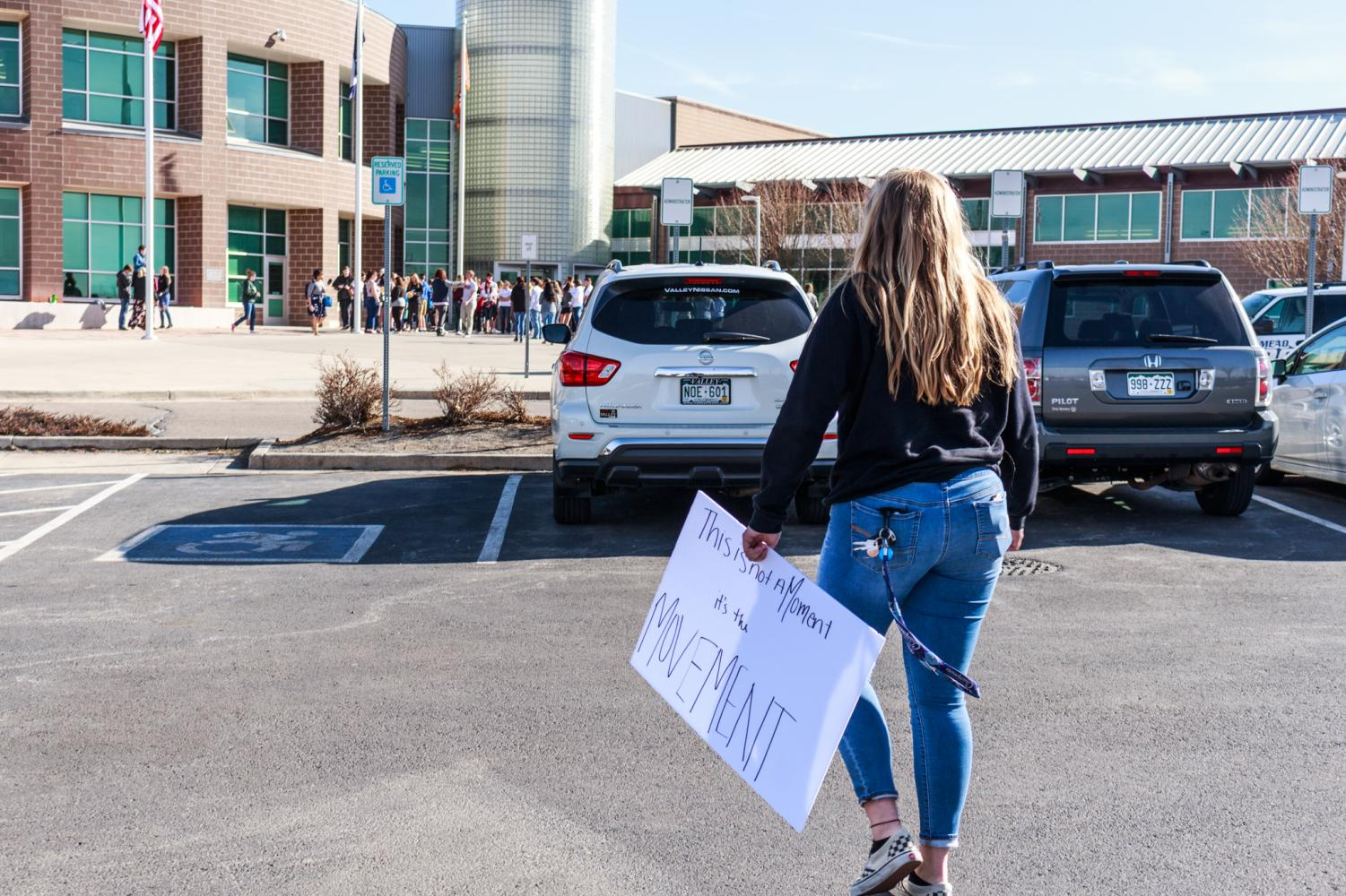 Junior Maddo Adams carries a sign to the walkout.