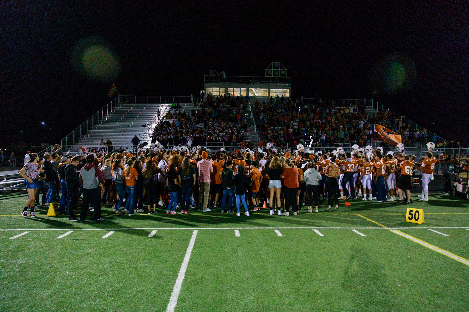 The+student+section+and+football+section+gather+on+the+field+together+as+the+band+plays+the+fight+song.