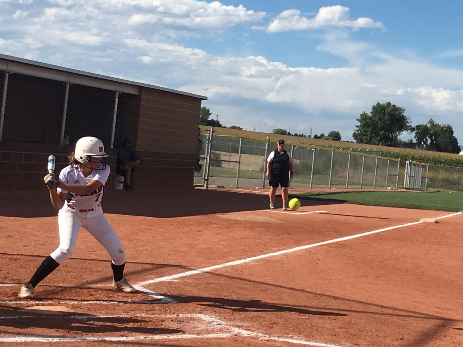 Freshman Maddox Boston (#7) prepares to swing as the ball is pitched at the softball game against Windsor on September 11.