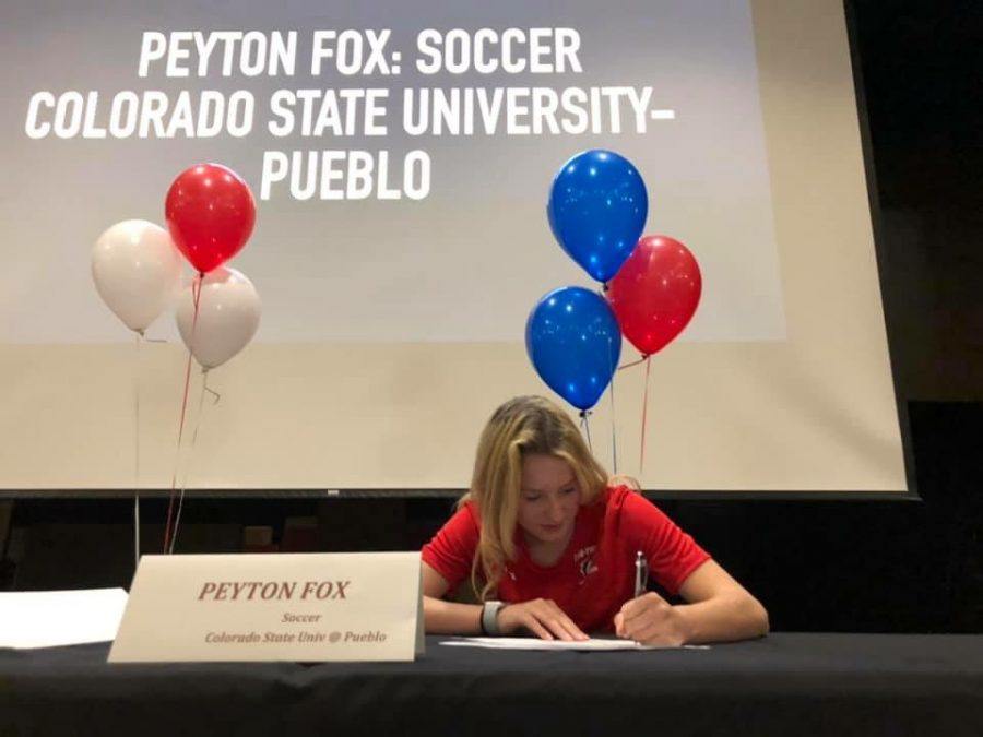Fox+signs+her+commitment+letter+in+the+Mead+High+auditorium.+