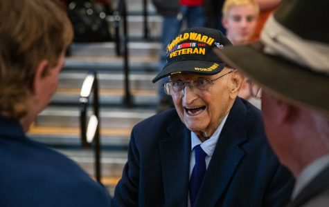 Tom Meylor, a World War II veteran, is greeted by those in attendance at the Veterans Day assembly.