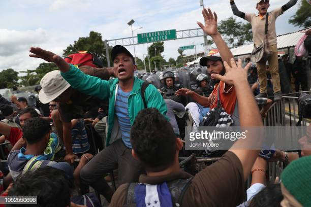 CIUDAD+TECUN+UMAN%2C+GUATEMALA+-+OCTOBER+19%3A++Members+of+the+migrant+caravan+try+to+slow+the+the+flow+of+thousands+of+fellow+immigrants+before+the+group+clashed+with+Mexican+riot+police+at+the+border+between+Mexico+and+Guatemala+on+October+19%2C+2018+in+Ciudad+Tecun+Uman%2C+Guatemala.+Migrants+and+Mexican+police+clashed+when+the+caravan+of+thousands+of+migrants+tried+to+cross+into+Mexico+after+pushing+past+Guatemalan+security+forces.++%28Photo+by+John+Moore%2FGetty+Images%29
