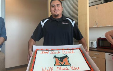 Campus supervisor David Morales poses with his going away cake, accurately scripted with