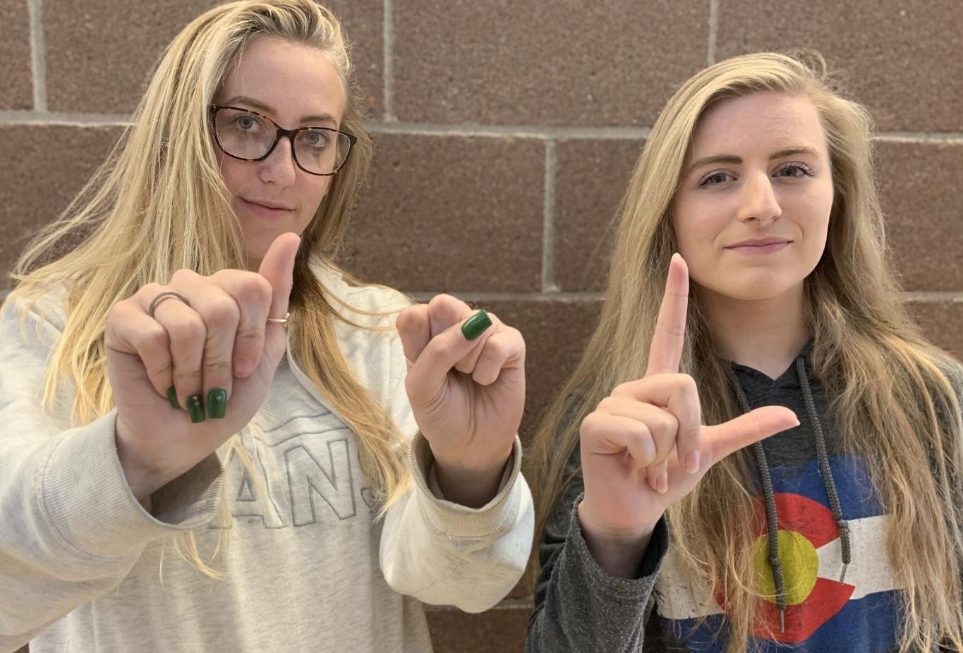 Andrea Randolph and Maddie Martenson, two previous ASL students from Mead, spell out ASL in sign language.