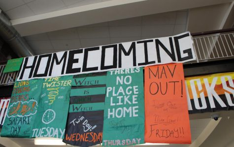 Student Council hangs posters reminding students of sprit week festivities.