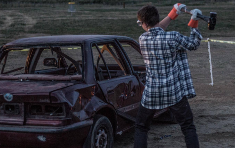 A student takes a sledgehammer to the car from the 2017-2018 school year.
