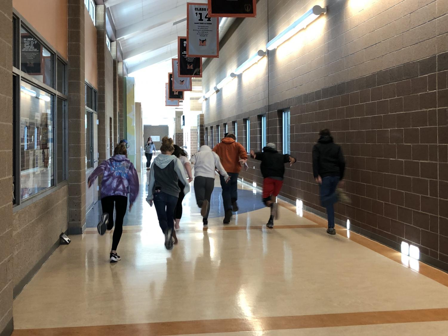 """A group of Freshmen students, acting as """"The Stompers"""", running down the hall to the cafeteria."""