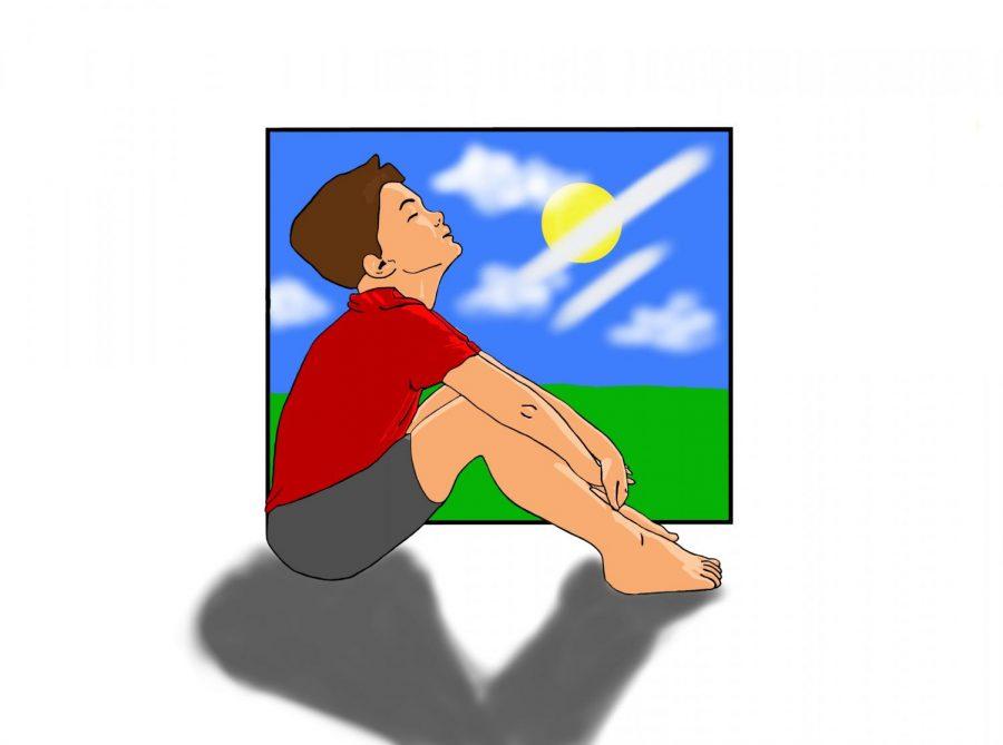 A boy sitting in the sun.