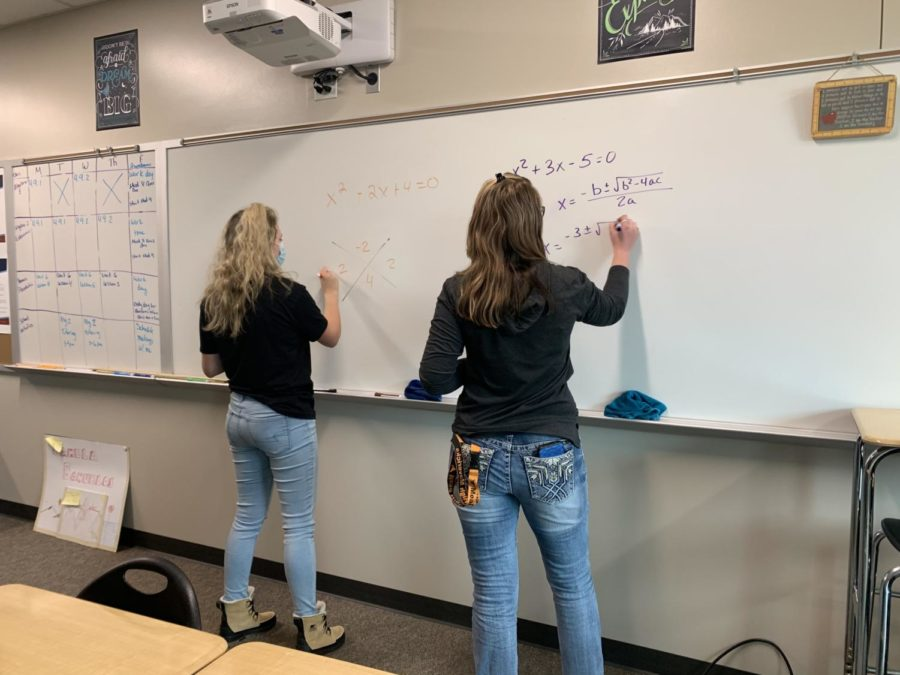 Ms. Goshia and Ms. Olson help show students how to factor and solve a problem with the quadratic equation.