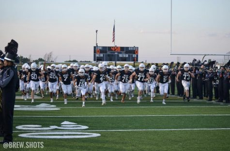 The Mead High School football team storms the field after the national anthem. Photo by Ryan Brewster! Check him out @brew.shots on instagram